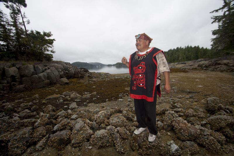 Native Watchman Tom Sewid stands on the low rock wall of an ancient clam garden.  Photo © Katya Palladina