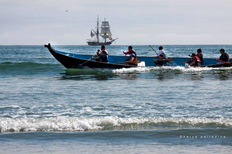 A traditional Northwest Coast canoe paddles through the surf.  The square rigger Lady Washington, visible in the background, acted as a support vessel for the Canoe Journey.
