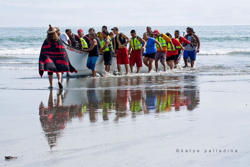 Paddlers guide a canoe onto the beach.