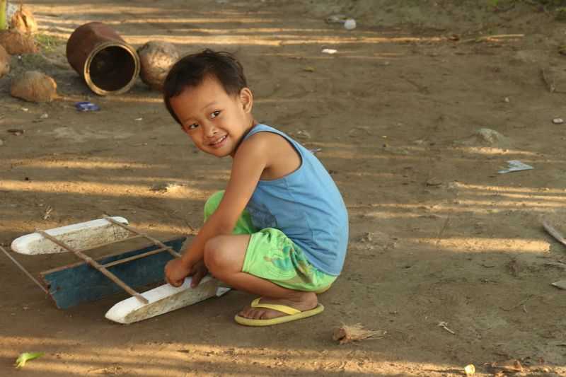 A boy in the fishing village plays with a toy model banca.
